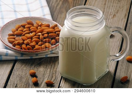 Almond Milk Cocktail In Jar With Almond Nuts On Rustic Wooden Table. Vegan Alternative Food, Non-dai