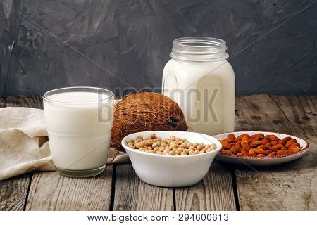 Glass Cup And Jar Of Vegan Plant Milk And Almonds, Nuts, Coconut, Soya Milk On Wooden Table. Dairy F