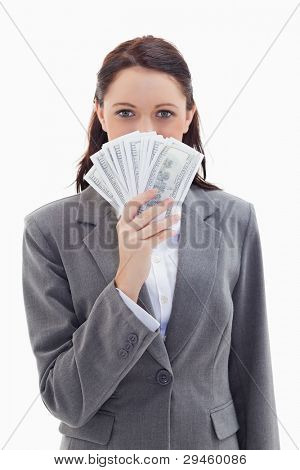 Close-up of a businesswoman hiding behind a lot of dollar bank notes against white background