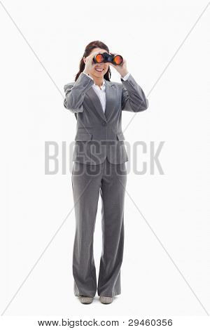 Businesswoman smiling and looking through binoculars on the left side against white background
