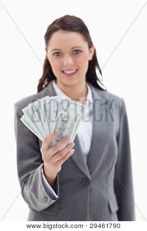 Close-up of a businesswoman smiling and holding a lot of dollar bank notes with focus on bank notes against white background