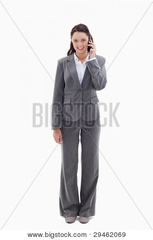 Smiling businesswoman using a phone against white background