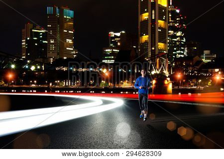 Young Sports Man Running on the Night City Road with Cars Light Trails. Healthy Lifestyle and Urban Active Sport Concept.
