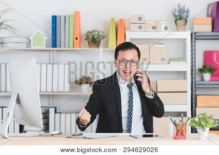 Portrait Of Young Handsome Asian Businessman Wearing Eyeglasses In Dark Suit, Working In Modern Star