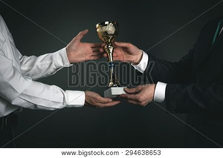 Award Ceremony Concept. Businessman Is Giving A Golden Cup Award Trophy To A Winner. First Place Bac