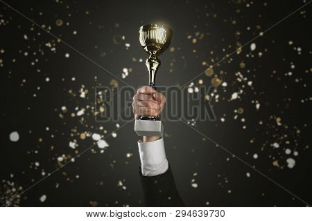 Businessman With A Golden Cup Award Trophy In Hand. First Place Concept Background. Best Worker Awar