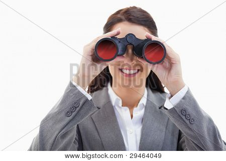Close-up of a businesswoman smiling and looking through binoculars against white background
