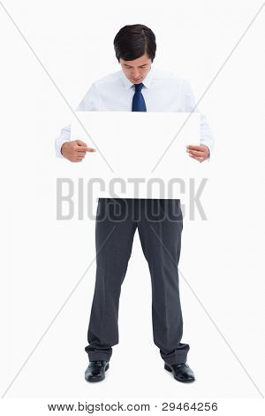 Tradesman pointing at blank sign in his hand against a white background