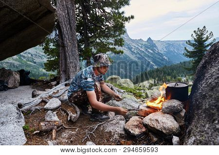 Man Built A Campfire In The Woods In Nature. Survive In The Mountains In The Forest, Cooking In A Po