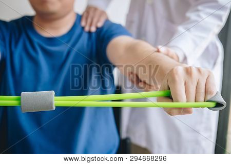 Doctor Physiotherapist Assisting A Male Patient While Giving Exercising Treatment On Stretching His