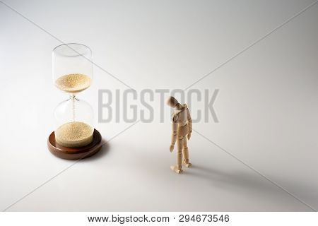 How Time Flies,miniature Wooden Mannequin Standing In Front Of An Hourglass Or Sand-glass,lower Its