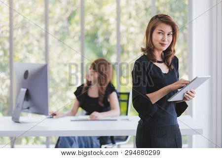 Beautiful Asian Successful Businesswoman In Black Dresses Standing And Look At Camera In Modern Offi