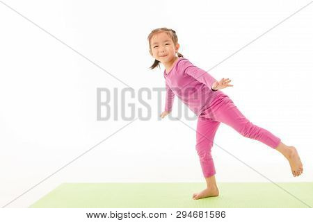Portrait Of Cute Little Asian Girl In Purple T-shirt And Pants Joyfully Doing Basic Yoga Exercise On
