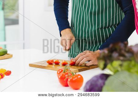 Close Up Of Man Hands Cutting Tomato On Cutting Board With Small Size Or Grape Tomatoes On White Kit