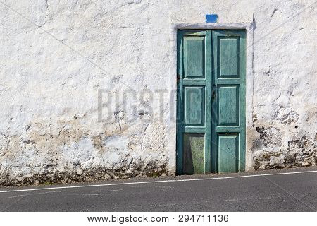 Old Green Door And A White Plastered Wall Near A Hillside Asphalt Road On Lanzarote In Spain