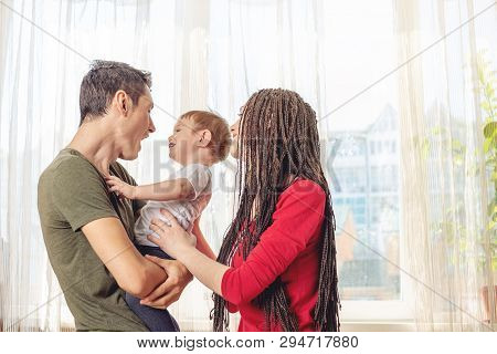 Happy Parents Father And Mother Playing With Baby Son At The In The Morning. Cheerful And Modern You