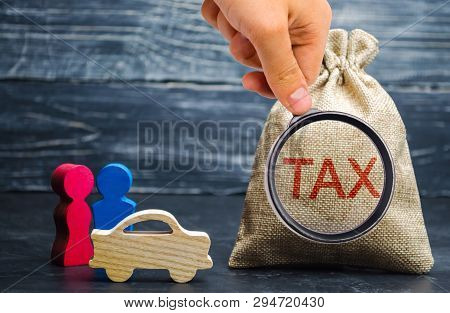 A Bag With Money And The Word Tax And A Car With Family. Concept The Taxes Payment For Auto. Vehicle