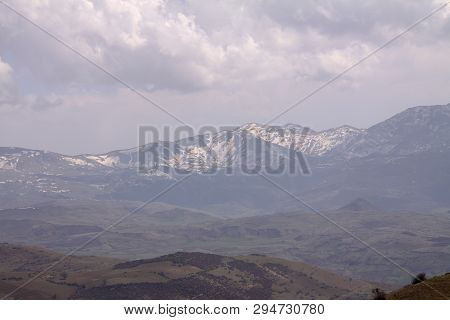 View Over The Hill With Mountain Trail And Snowy Mountains On The Background. Beautiful Mountain Tra