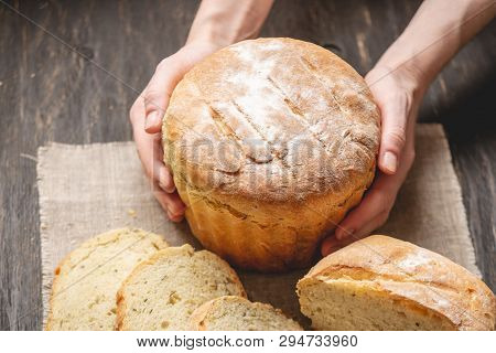 Female Hands Holding Homemade Natural Fresh Bread With A Golden Crust On A Napkin On An Old Wooden B