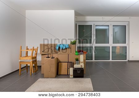 Bright, Large Room With Moving Boxes And Rolled-up Carpet During Move-in