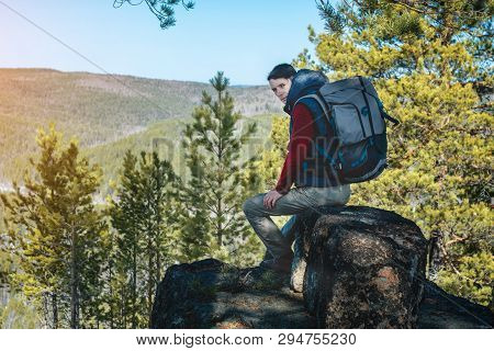 Man Hiker With A Large Backpack Sitting On A Rock Cliff And Looking At The Sprawling Green Valley. F