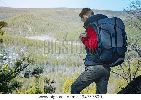 Man Tourist With A Large Backpack Stands On A Rock Cliff And Looking At The Sprawling Green Valley.