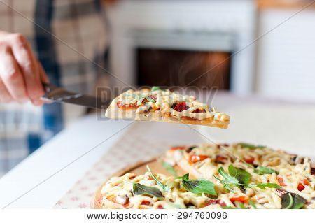 Woman Holds Steamy Slice Of Hot Pizza In Cozy Home Kitchen. Cooking Process Of Italian Family Dinner