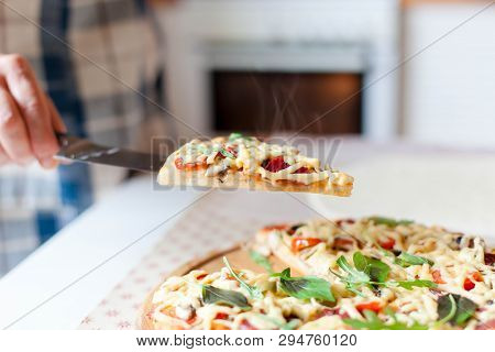 Woman Holds Steamy Slice Of Hot Pizza In Cozy Home Kitchen. Cooking Process Of Italian Fasdt Food At