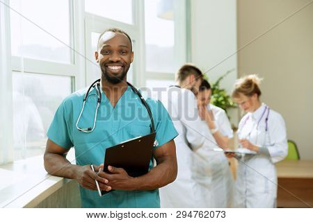 Healthcare People Group. Professional African American Male Doctor Posing At Hospital Office Or Clin