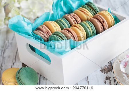 Assortment Of Fresh French Macarons Packaged In A Pretty White Wooden Box With Blue Tissue On A Whit