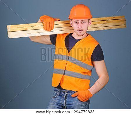 Carpenter, Woodworker, Labourer, Builder On Confident Face Carries Wooden Beams On Shoulder. Hardy L