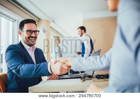Close-up Of Business People Handshaking In Modern Office
