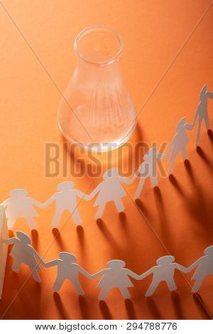 Circle of paper people holding hands in front of empty glass vial. Water scarcity global problem. Dependency, addiction concept.