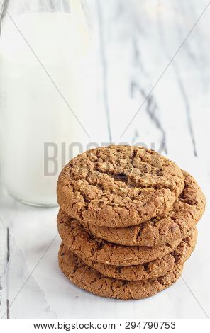 Overhead Shot Of Stack Of Fresh Homemade Oatmeal Cookies With A Bottle Of Milk On A White Table Agai