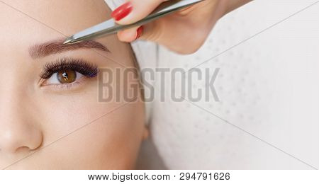 Beautiful Young Girl With Long Eyelashes Tweezing Her Eyebrows In A Beauty Salon. Woman Doing Eyebro