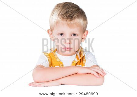 Obeying Young Boy Sitting At Table Isolated On White