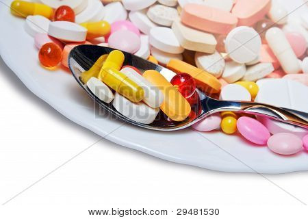 Lot Of Colored Pills On Plate And Spoon