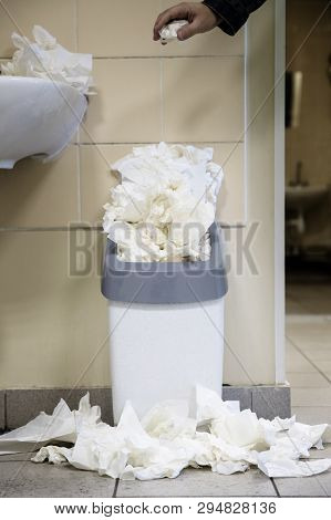White used paper tissue in overcrowded bin/Male hand drops paper tissue in full trash bin/utilized toilet paper dropped around the trash basket, vertical/ Dirty toilet concept poster