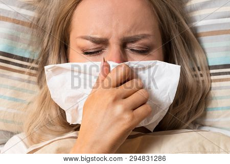 Young European Upset And Sick Woman With Paper Napkin Blowing Nose, Lies On The Pillow Under The Bla