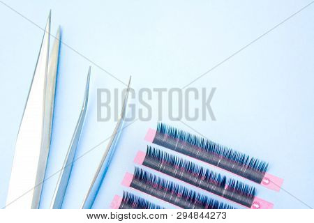 Tools For Eyelash Extension Procedure. Two Tweezers With False Lashes On Blue Background. Copyspace