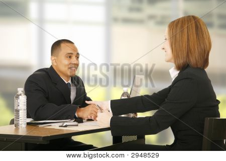 two business people shaking hand over table. focus on the woman. concept for business deal team work selling or agreement poster