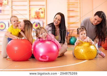 Happy Mothers And Nursery Babies On Fitness Ball In Gym. Gimnastics For Kids On Fitball.