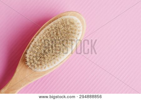 Wooden Brush For Dry Anticellulite Massage On Pink Background. Body Care Concept