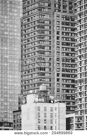 Black And White Picture Of A Water Tower On A Rooftop.