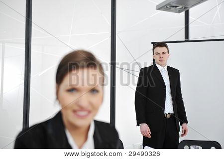 Young businessman and businesswoman in business presentation at office, looking at camera smiling