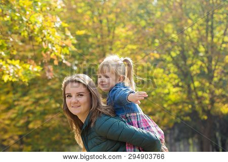 Happy Mother Playing With His Daughter In The Park  In Summer Day