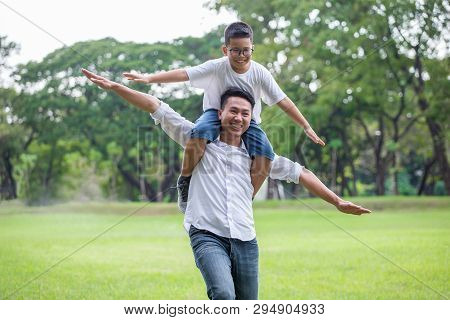 Happy Asian Family .father And Son Runing , Playing And Stretching Out Hands Together In The Park .