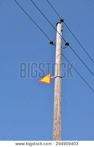 Wooden Post With Power Lines And A Warning Sign By A Blue Sky