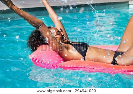Happy young fashion woman in bikini with rubber inflatable float and having fun with water at swimming pool. Smiling african girl splashing water in resort pool. Beautiful black lady relax at pool.