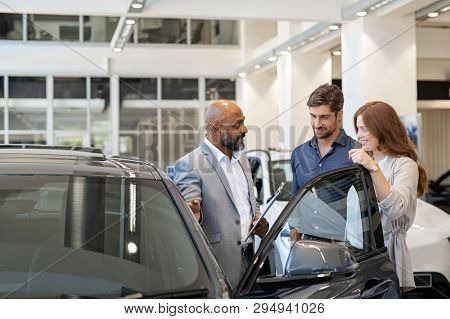 Beautiful couple smiling while examining a new car in a motor show with salesman. Mature salesman showing new luxury car to man and woman in showroom. Happy couple with cardealer showing new features.